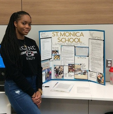 Female student standing beside her display