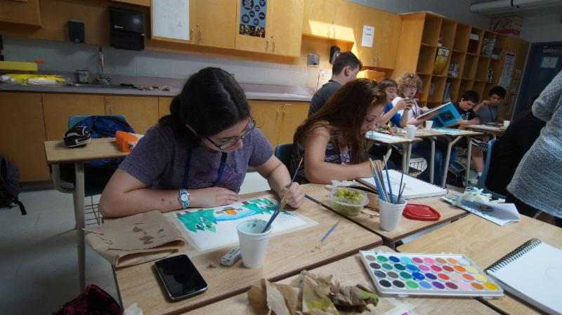 Female and male student painting in an art classroom