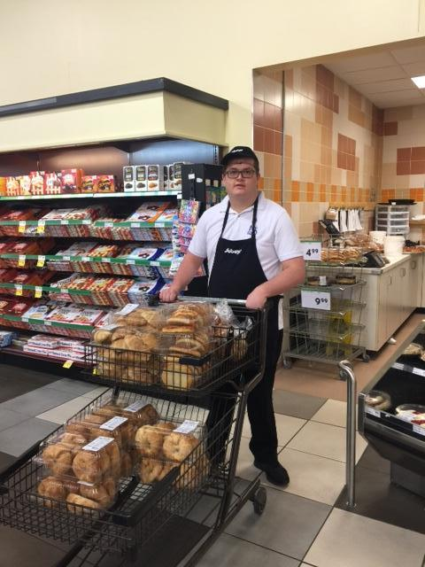 male student working in grocery store taking baked goodies in shopping cart to the restock the floor