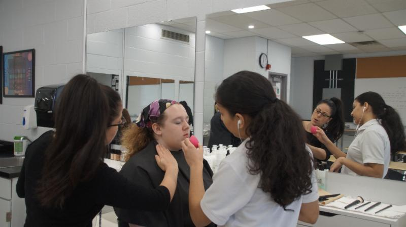 High school teacher providing some tips to student who is applying make up to another female student