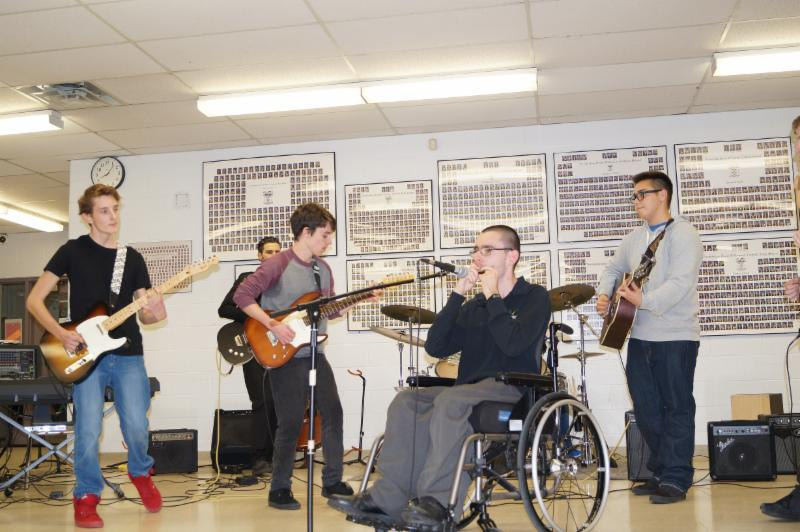 Five male students on stage playing musical instruments