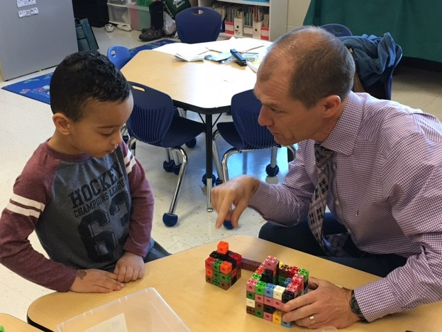 Male adult talking with male student about math