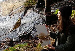Female student holding a picture of her landscape oil painting in nature.