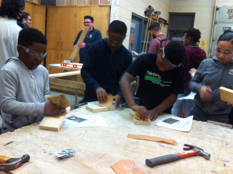 Male and female students working in a woodworking classroom