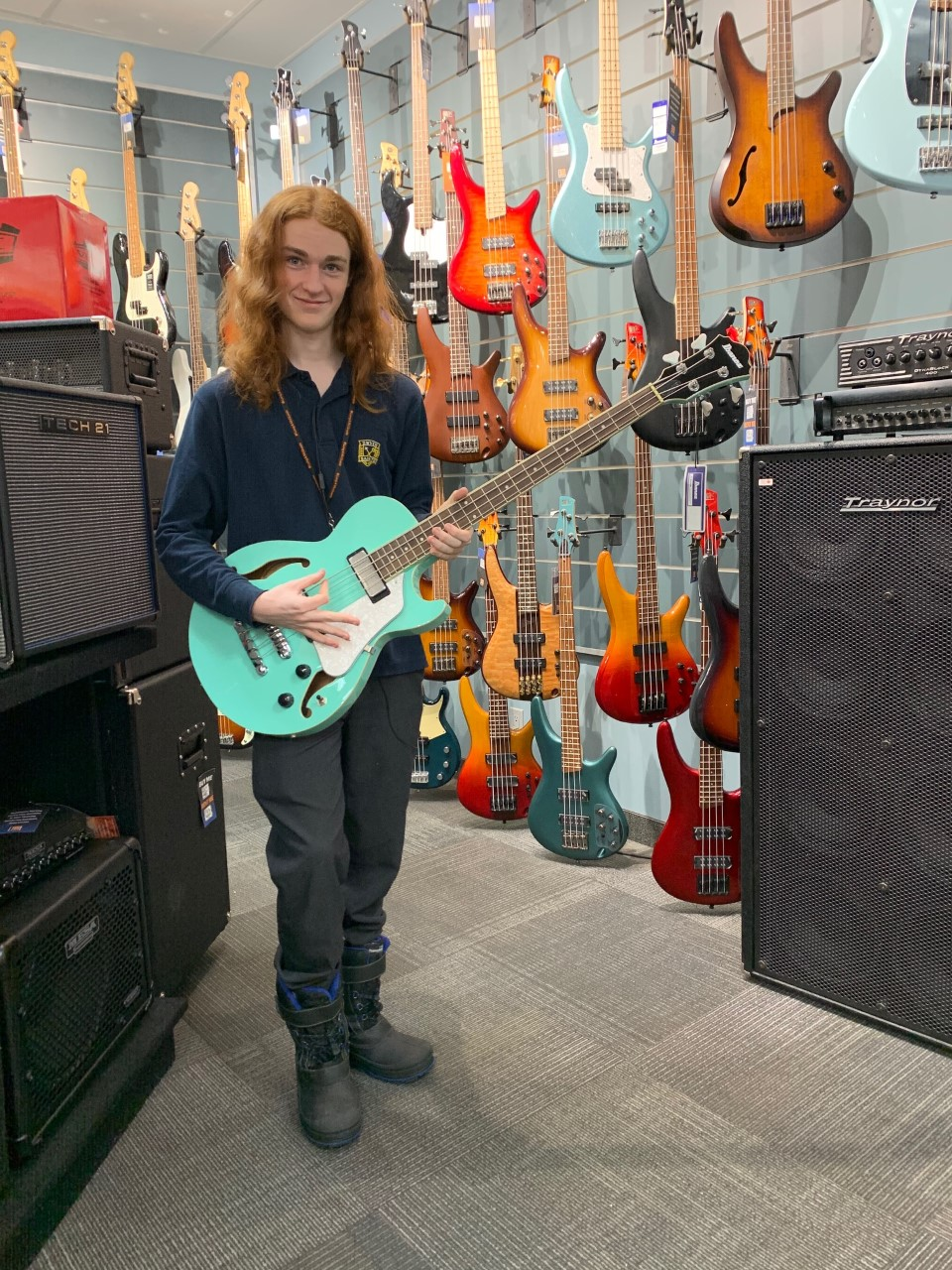 Male student holding a guitar in a music store