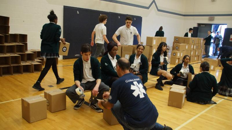 Male and female student taping up the kits in cardboard boxes