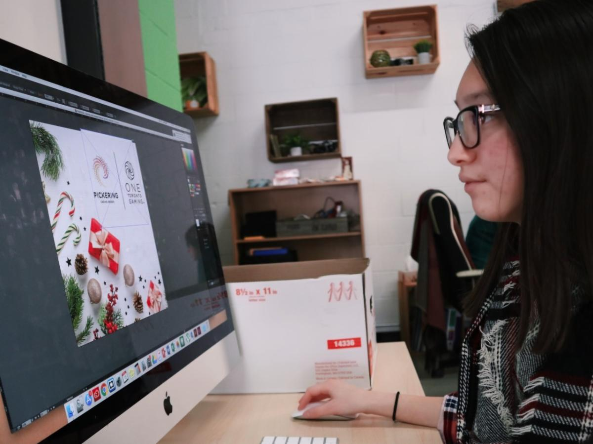 Female student working on a MAC computer designing an invitation.