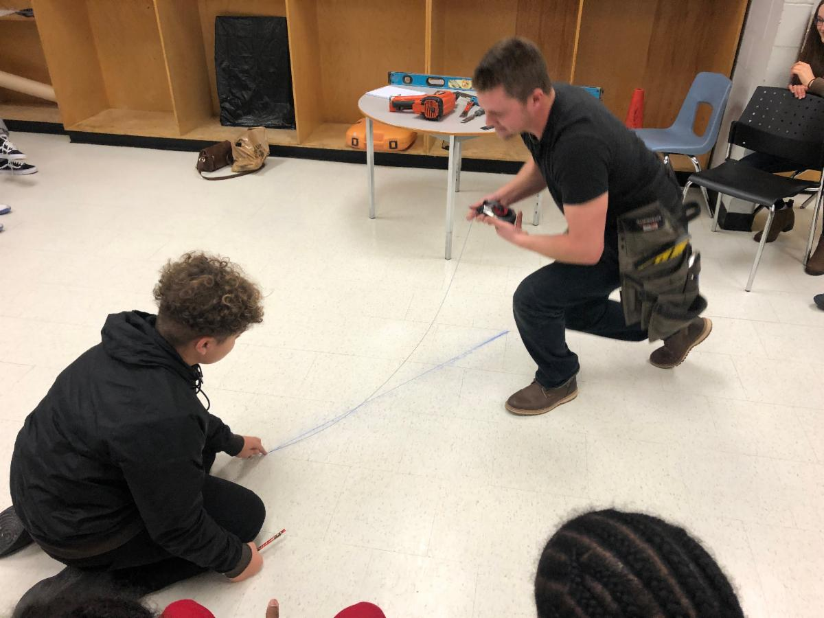 Male student and adult making a chalk line on the floor