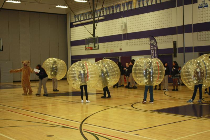 Students wearing bubble costumes in a gym