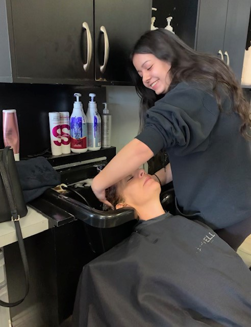 Female student washing a female adults hair in a salon as part of her cooperate placement.