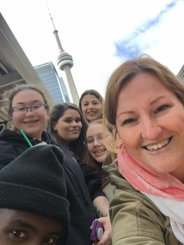 Female teacher with four female and one male student taking a selfie in Toronto with CN Tower in the background.