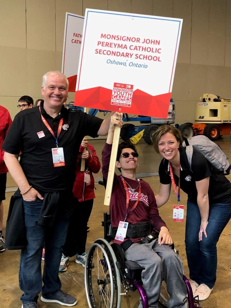Male student in wheelchair holding school sign with male and female adult coaches