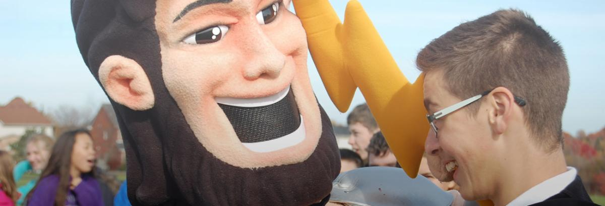 Male student face to face with school mascot
