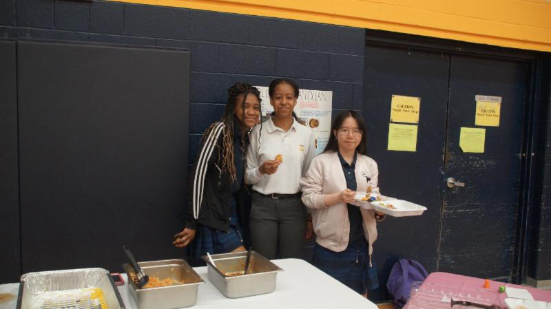 Three female students standing together eating