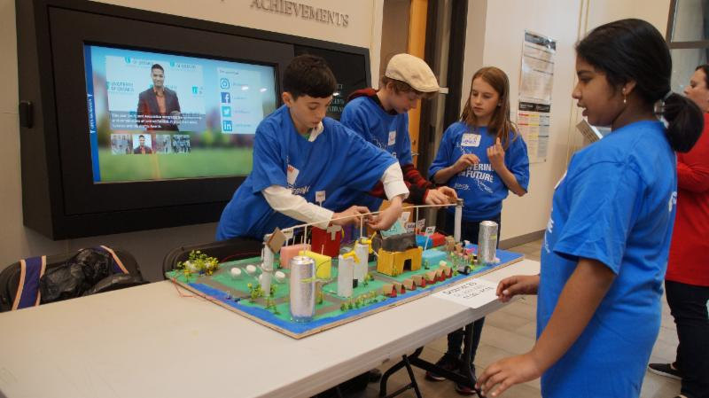 Male student putting finishing touches on team's future city model