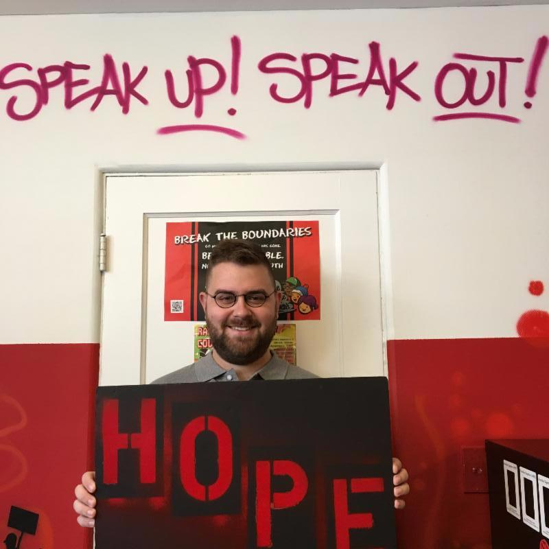 Zack Kilmer holding a red and black hope board, standing below the words Speak Up! Speak Out!