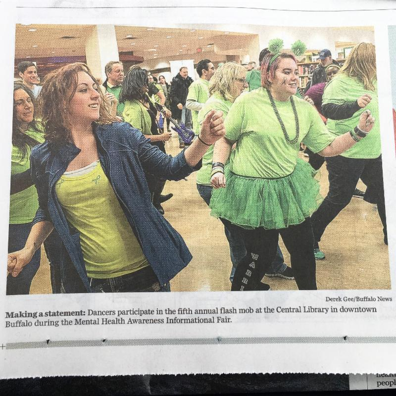 photo of newspaper article with the flash mob dancers. caption reads Making a statement_ Dancers participate in the fifth annual flash mob at the central library in downtown buffalo during the mental health awareness informational fair