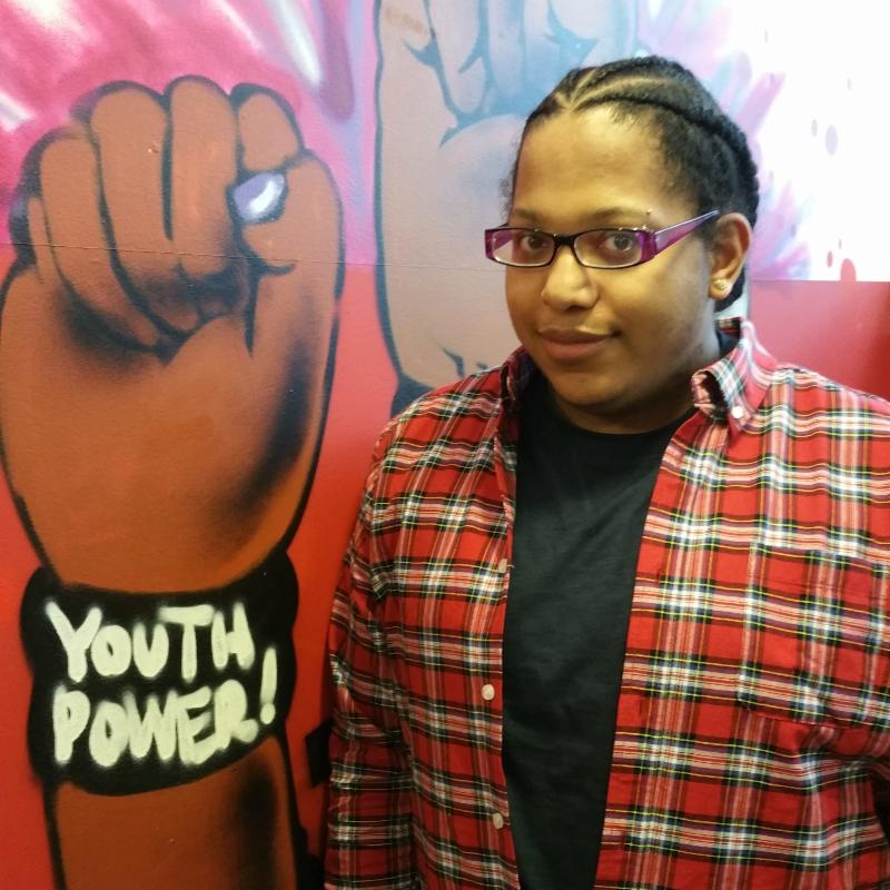 Peterson Rodriguez standing in front of a graffiti style wall with solidarity fists and a YP! wristband around the wrist