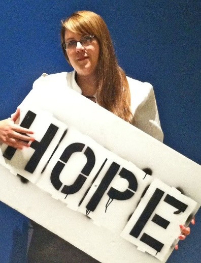 Stephanie Orlando posing with the Hope board