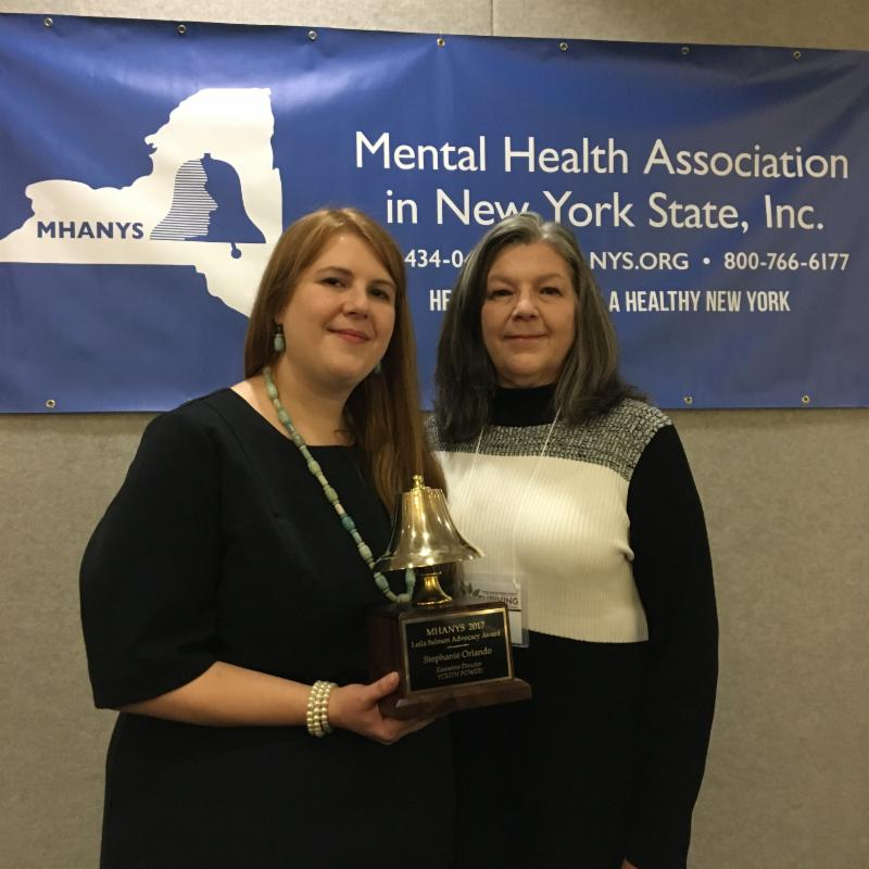 Stephanie Orlando and her mother, Diane, posing with the award in front of the MHANYS banner
