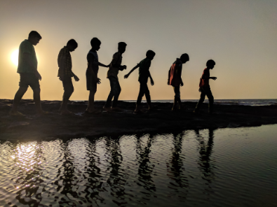 7 youth walking on a beach with their silhouettes