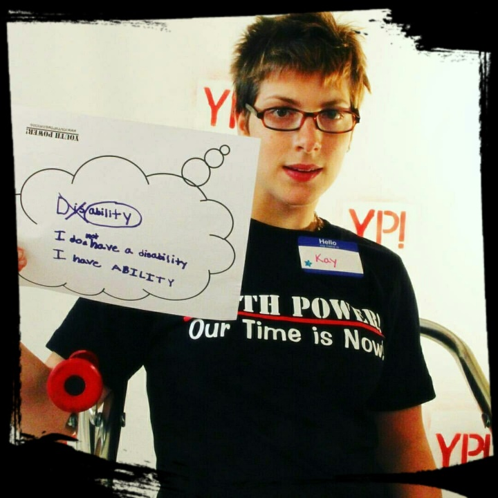 photo of Kaylin wearing a YOUTH POWER_ shirt and holding a sign that states _ I don_t have a disability_ I have ABILITY_