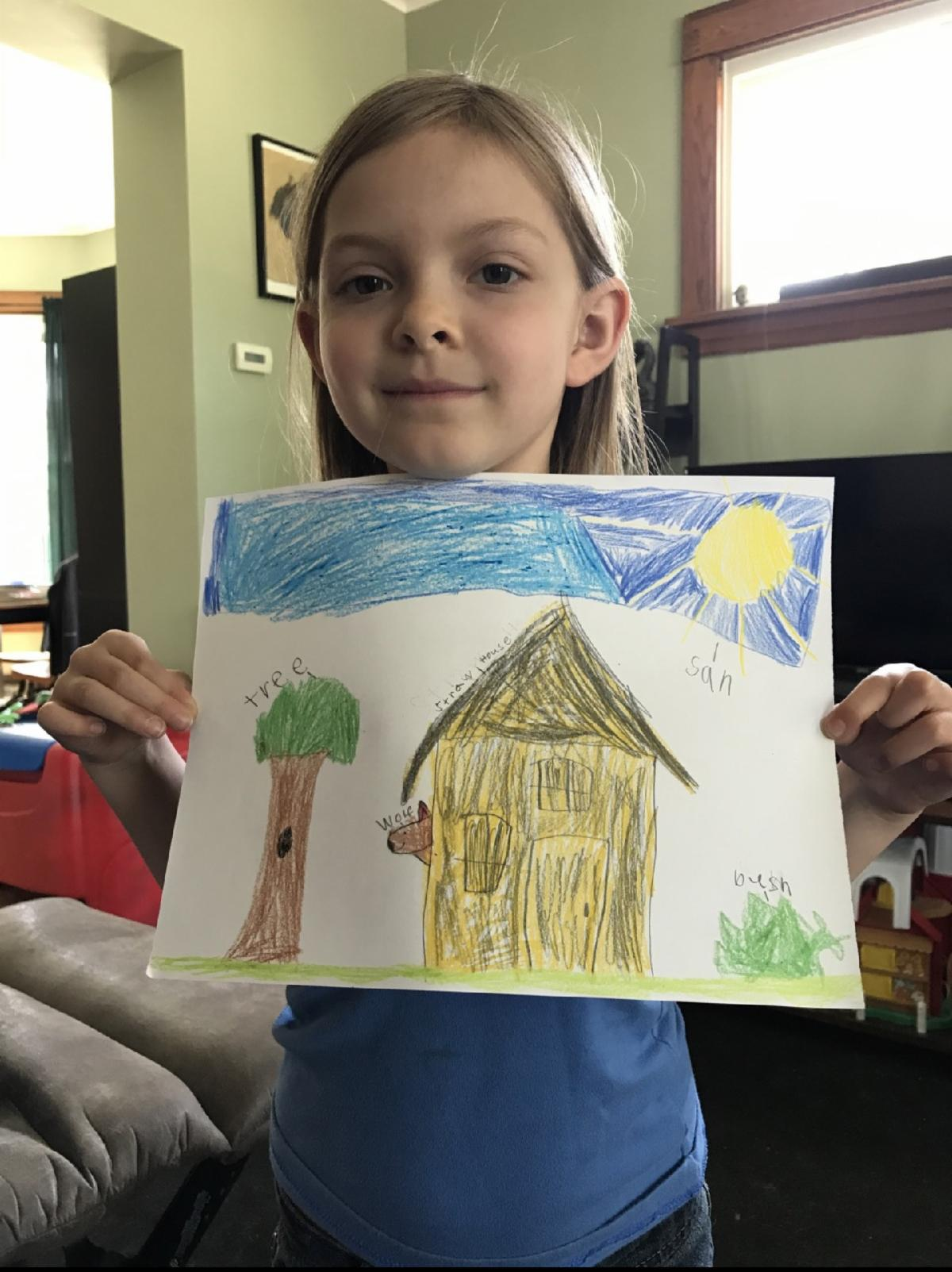 Young girl holding homemade art drawing of house, tree and sky with sun