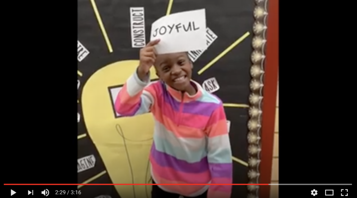"Smiling girl holding her ""one word"" sign - Joyful"