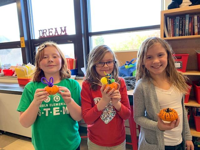 Three Lincoln students holding mini pumpkins