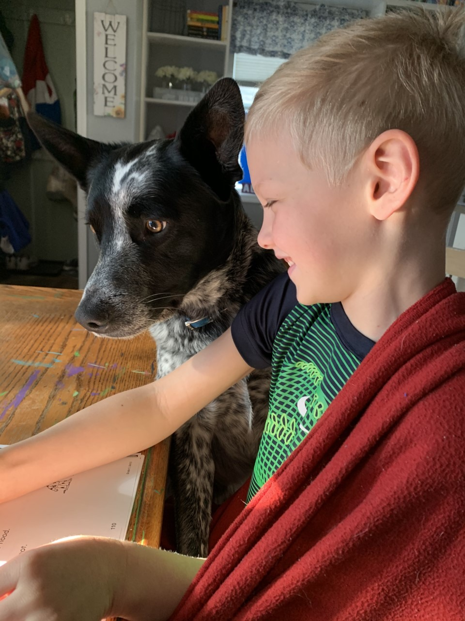Smiling boy with dog at table