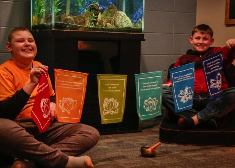 Two young men with singing bowl and mindfulness banners
