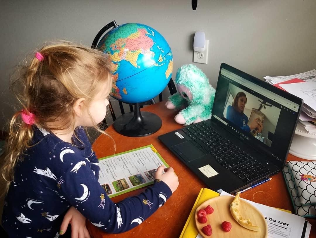 Young girl working with teacher via laptop at home