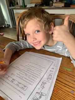 Lincoln boy giving thumbs up while doing homework at home