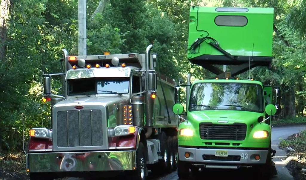 Two industrial trucks side by side with trees in background