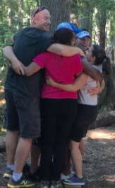 People embracing around a tree