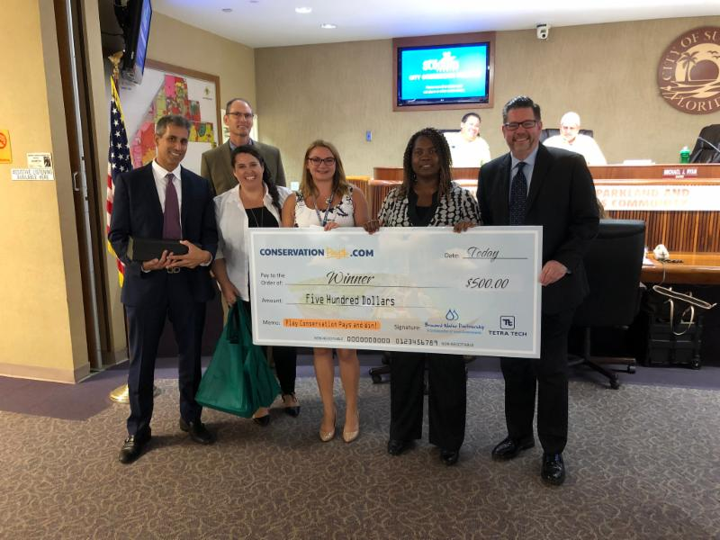 Mayor presenting large check to ConservationPays winner