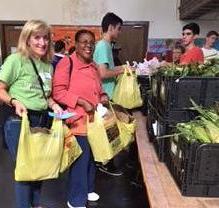 Investors Bank volunteer escorts client through Farmers Market