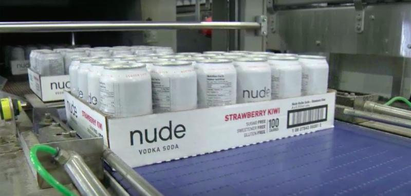 nude vodka soda cans on conveyor belt