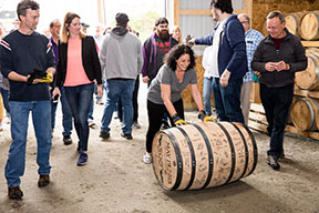 Wiggly Bridge Distillery fans taking turns rolling the barrel to the newly built rickhouse behind the distillery.