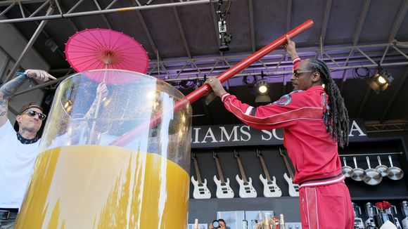 Snoop Dogg stirs the world_s largest paradise cocktail after adding gin to it on a culinary stage at the BottleRock Napa Valley music festival in Napa_ Calif._ alongside Top Chef Michael Voltaggio.