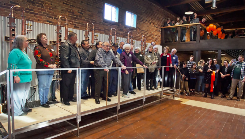 Members of prominent Roslyn families stand in front of stills that honor their family names at Heritage Distilling in Roslyn during a grand opening celebration this month.