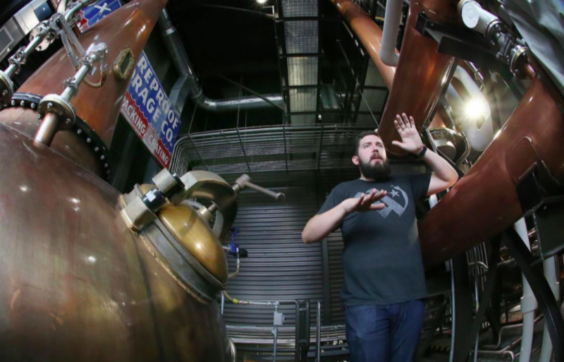 Tommy Mote_ who works in brewing at Balcones_ stands between the existing copper stills.