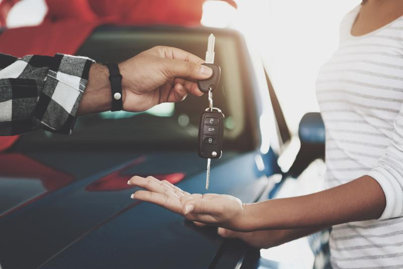 Close up man is giving keys to woman. African american family at car dealership. Father_ mother and son near new blue car.
