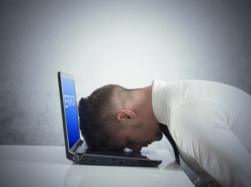Businessman with blue screen of laptop error