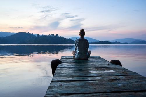 Peaceful lifestyle shot of woman sitting on dock at sunset on Lake Bunyonyi_ Uganda_ Africa.
