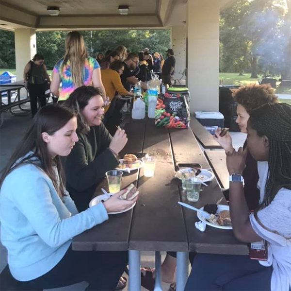 photo of students eating at a picnic table in a park shelter