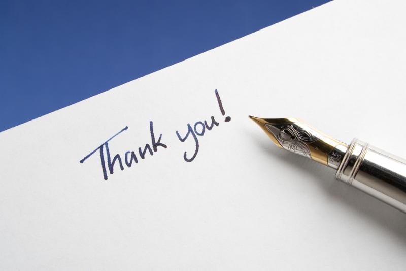 Fountain Pen with Thank You Note hand written on page on blue background
