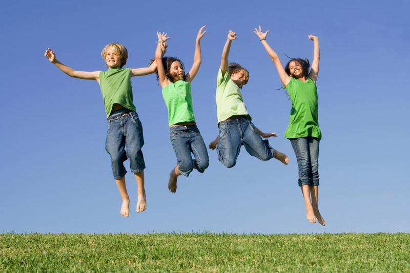 happy group of kids children twins youth jumping for joy at summer camp