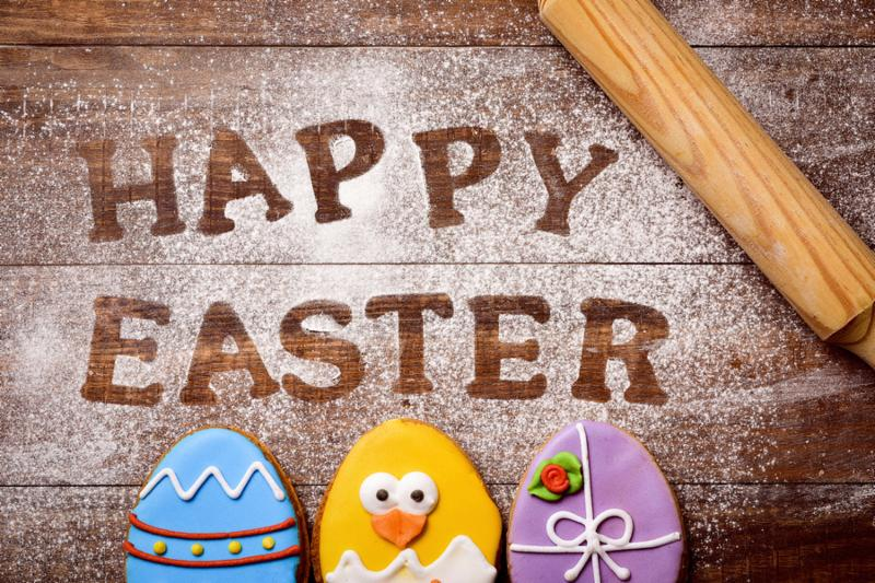 high-angle shot of a wooden table sprinkled with icing sugar or flour where you can read the text happy easter, cookies decorated as ornamented easter eggs and a funny chick, and a rolling pin