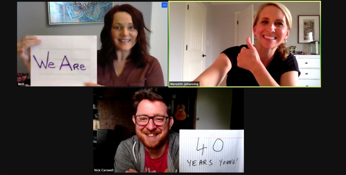 """A screen shot of a zoom call. Beth McKenzie is holding up a handwritten sign that says """"We Are"""". Meredith Johanning is smiling and making the thumbs up sign. Nick Carswell is holding up a handwritten sign that says """"40 years young!"""""""
